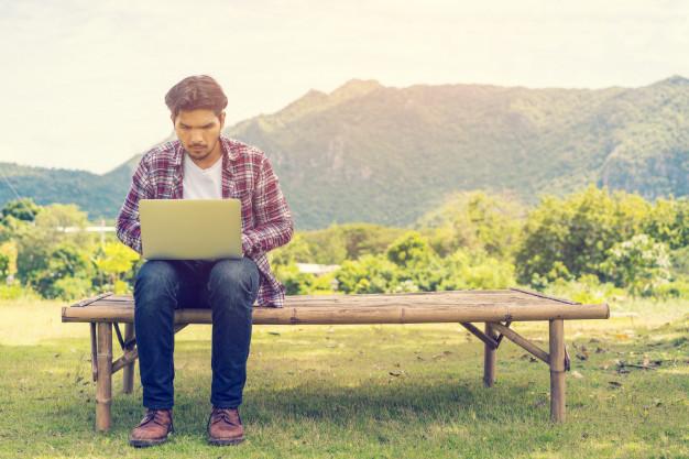 hombre-joven-que-trabaja-su-computadora-portatil-conecta-internet-inalambrico-area-rural_31965-453